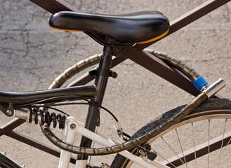 vélo en ville accroché à une grille par un antivol