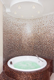 White round jacuzzi in modern bathroom with brown mosaic and cou