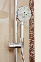Metal shower tap in modern bathroom with brown ceramics tile