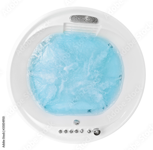 Round jacuzzi with swirling blue water isolated on white