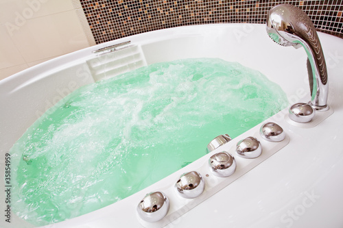 Jacuzzi with swirling water and brown mosaic in bathroom