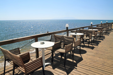 Idyllic cafe restaurant by the sea, on wooden deck