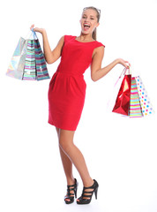Sexy happy woman in red dress shopping gift bags