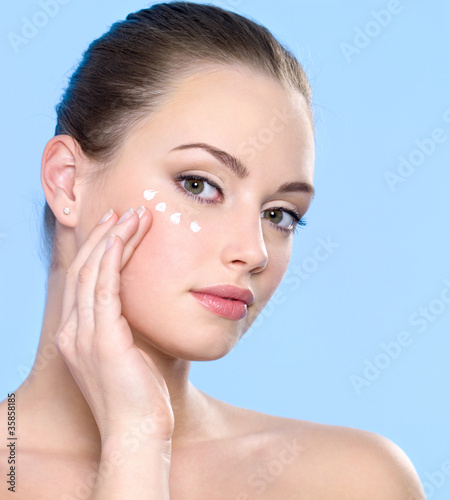 woman applying cream on skin around eyes
