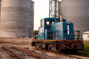 Train head car stopped on tracks in front of grain mill