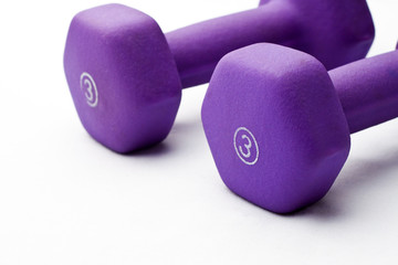 A pair of 3 lb purple neoprene weights beside each other