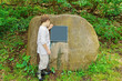 Boy Looking at Blank Sign on Boulder
