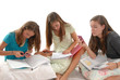 Three teenage girls doing homework books phones