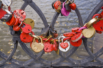 Разноцветные свадебные замки на парапете моста