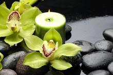 bougie allumée et pierres zen avec orchidée jaune