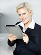Smiling woman in the office is working with touchpad