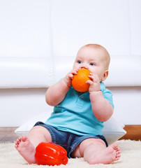 Toddler biting an orange