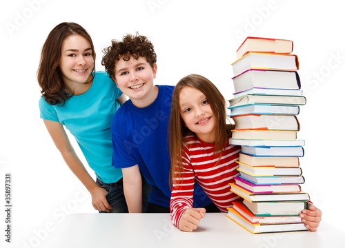Students behind pile of books and peeking