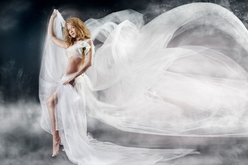 Beautiful woman with flying white chiffon fabric a wind flow. Fa