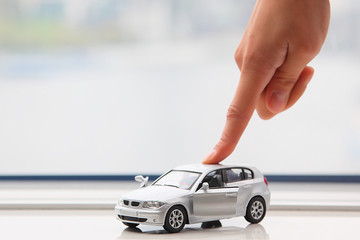 The finger moves the toy car
