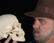 A Man in a Fedora Examines a Skull