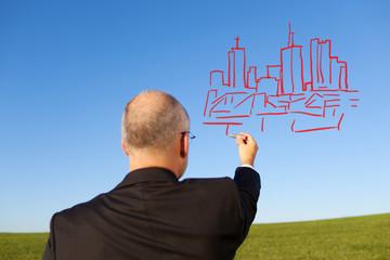 geschäftsmann zeichnet skyline in den himmel