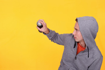 teenager wearing hoodie against yellow background holding spray