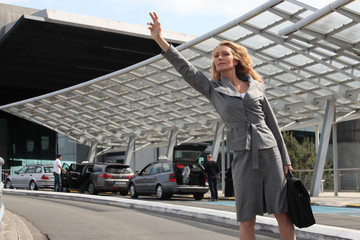 Businesswoman waving taxi