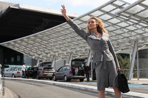 Businesswoman waving taxi