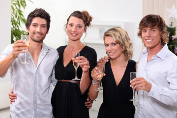 four people toasting in front of a Christmas tree