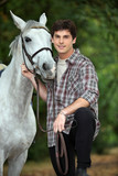 young man taking care of his horse