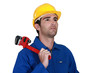 pensive electrician holding adjustable spanner