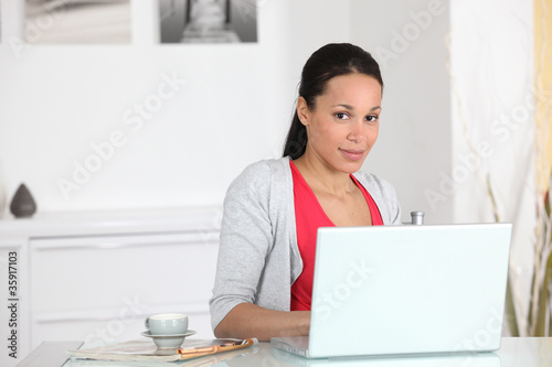 Woman sat with cup of coffee by laptop