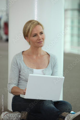 Casually dressed woman using a laptop computer in a public space