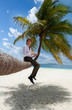 Businessman with tablet pc sitting on palm tree