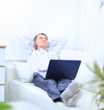Senior man in sofa with laptop computer