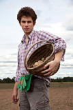 young handsome farmer on the field during harvest season