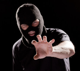Burglar in mask, robbing something by  hand