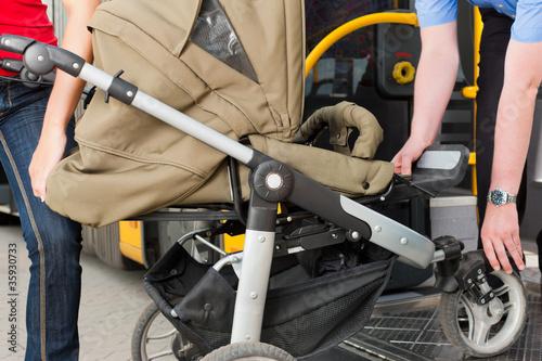 Frau mit Kinderwagen steigt in Bus ein