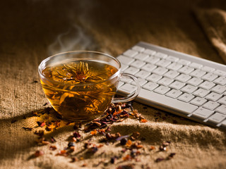 hots steaming jasmin tea and keyboard on table