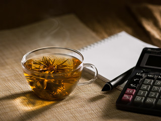 hots steaming jasmin tea and calculator on table