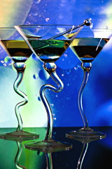 Three martinis in glasses with curved stems in front of colorful