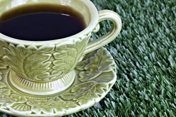 Coffee cup and saucer in grass