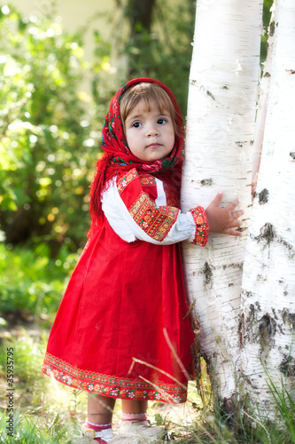 little girl in the Russian national dress embraces a birch