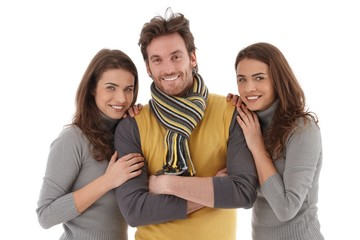 Beautiful female twins embracing handsome man