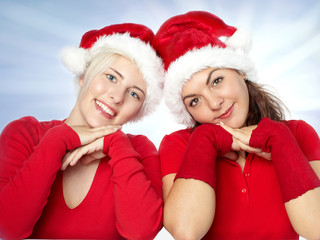Pretty girls with santa hat has fun in front of blue sky