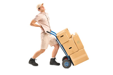 Delivery boy, suffering from a back pain, pushing a hand truck
