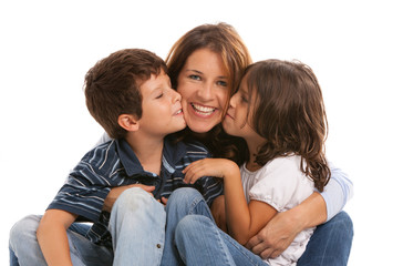 Son and daughter kissing mother on a white background