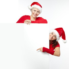 Two beautiful women with santa hat presenting copyspace