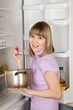 woman eating  from pan near  refrigerator