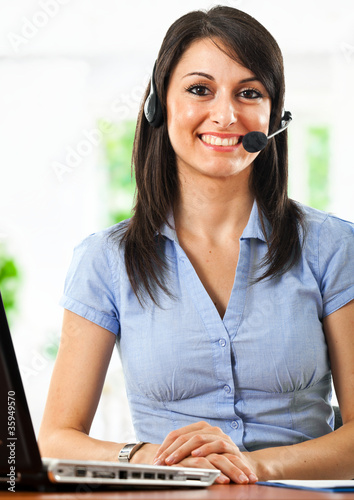 Smiling call center girl working on the laptop