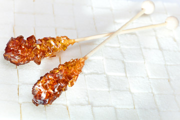 candy brown sugar on a stick lies on white lumpy sugar..