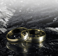 two golden wedding rings on ice surface
