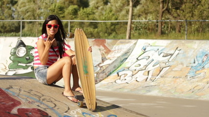 Asian skateboarder girl carrying her long board
