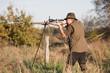 Jäger mit Fernglas, Waffe und Schießstock